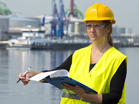 Female foreman turning a page on her clip board during her inspection rounds through an industrial harbor
